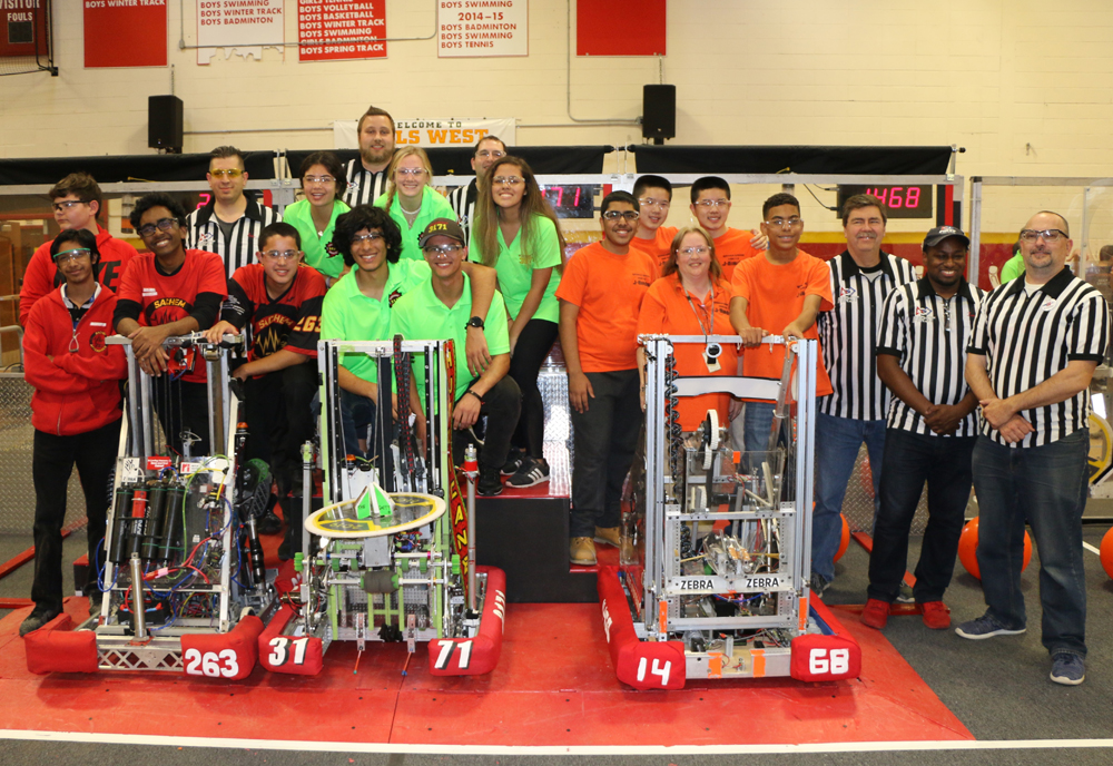 "The winning alliance of (left to right) Sachem High School Team #263 ""Sachem Aftershock,"" Westhampton Beach High School Team #3171 ""Hurricanes"" and Hicksville High School Team #1468 ""J-Birds"" is joined by event referees."
