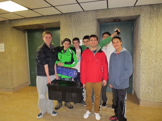 Members of the Wheatley High School robotics team pose with the contents of the kit of parts.