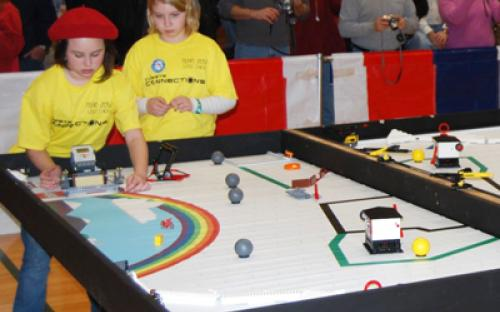 "Two members of the Girl Scouts of Nassau County in Hicksville – Team 2052 ""LEGO Chicks"" guide their robot on the course at the January 11 Long Island LEGO League Tournament."
